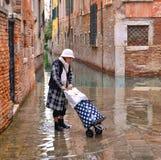 Женщина Trandy модная зрелая с гетрами, ботинками и чемоданом на полной воде в старой узкой затопленной улице стоковая фотография