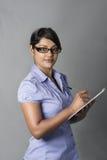 Женщина witing с ручкой на доске сзажимом для бумаги Стоковые Фото