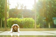 Женщина Yogi делает тренировки йоги, разработку, практикуя метод pranayama дышая Просторная комната с большими полнометражными ок Стоковые Фото