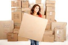 Женщина Yong двигая держащ пустую коробку при коробки штабелированные на заднем плане Стоковое Фото
