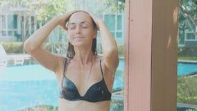Женщина Yong милая принимая ливень внешний на зоне бассейна в замедленном движении акции видеоматериалы