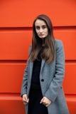 Женщина Yound на оранжевой стене Стоковые Фото