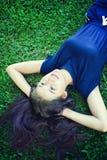 Женщины Азии ослабляя в зеленой траве Стоковая Фотография