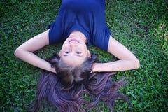Женщины Азии ослабляя в зеленой траве Стоковые Фото