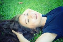 Женщины Азии ослабляя в зеленой траве Стоковое Изображение