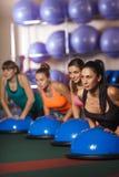 Женщины балансируя на шарике bosu Стоковые Изображения