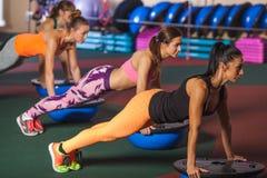 Женщины балансируя на шарике bosu Стоковое Фото