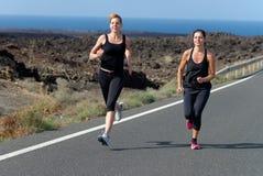 2 женщины бегуна бежать на дороге горы Стоковое Изображение RF