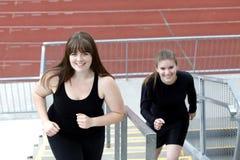 2 женщины бежать вверх лестницы снаружи Стоковая Фотография