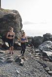2 женщины бежать на пляже около утесов стоковые фото