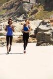 2 женщины бежать на пляже Стоковые Изображения RF
