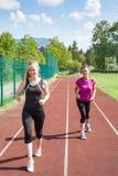 2 женщины бежать на следе совместно Стоковые Фото