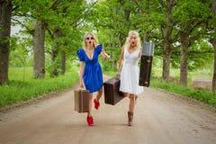 2 женщины бежать с suitecases в их руках Стоковое Изображение RF