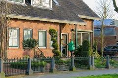 2 женщины беседуя на пороге в Meerkerk Стоковое Изображение