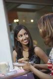 Женщины беседуя на таблице кафа Стоковая Фотография