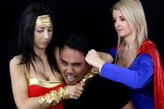 2 женщины бить человека Стоковая Фотография