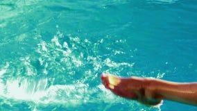Женщины брызгая ее ноги в бассейне видеоматериал