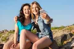 2 женщины, брюнет и блондинка, делают selfie на открытом воздухе Стоковое Изображение