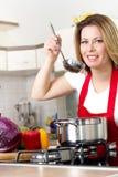 Женщины варя и испытывая еду в кухне Стоковые Изображения