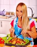 Женщины варя цыпленка на кухне Стоковые Изображения