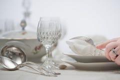 Женщины вручают аранжировать серебряный столовый прибор на таблице с фарфором d стоковые фото