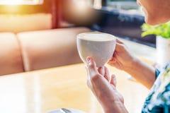 Женщины вручают держать горячие чашку кофе или чай в солнечном свете утра Стоковые Изображения