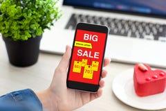 Женщины вручают держать телефон с большим экраном продажи на таблице Стоковая Фотография RF