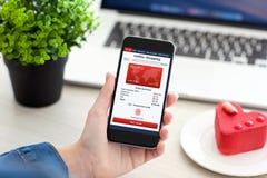 Женщины вручают держать телефон с покупками app онлайн на таблице Стоковые Фото