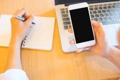 Женщины вручают используют телефон на пустом экране и пишут блокнот с ручкой в офисе стоковая фотография