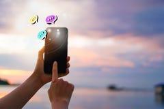 Женщины вручают используя переговор smartphone печатая в значках коробки болтовни хлопают вверх Социальные средства массовой инфо стоковые изображения