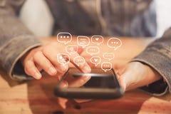 Женщины вручают используя smartphone печатая, беседуя переговор в значках коробки болтовни хлопают вверх Социальные средства масс стоковые фото