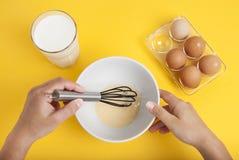 Женщины вручают смешивая яичка и молоко ингридиентов выпечки в взгляд сверху предпосылки желтого цвета подготовки десерта шара стоковое фото