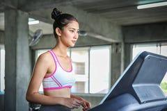 Женщины входят в программу управления веса Молодые люди бежать на третбане Тренировка молодой женщины в спортзале красивейше стоковая фотография