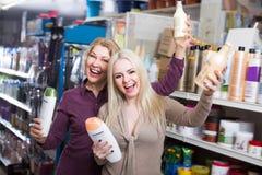 Женщины выбирают шампунь в косметическом магазине Стоковое Фото