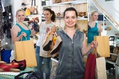 3 женщины выбирая ботинки в магазине Стоковое Изображение