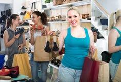 3 женщины выбирая ботинки в магазине Стоковые Изображения