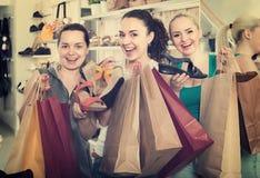 3 женщины выбирая ботинки в магазине Стоковая Фотография