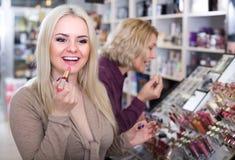 Женщины выбирая губную помаду на магазине Стоковое Фото