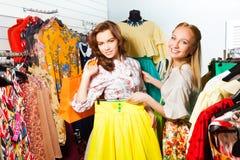 2 женщины выбирая желтую юбку в магазине Стоковое фото RF