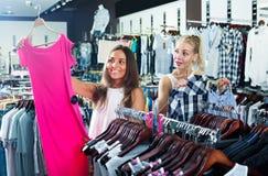 2 женщины выбирая новое платье в отделе моды Стоковые Фотографии RF