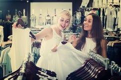 2 женщины выбирая новую блузку в магазине моды Стоковые Фотографии RF