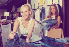 2 женщины выбирая новую пару джинсов в отделе моды Стоковое Изображение RF