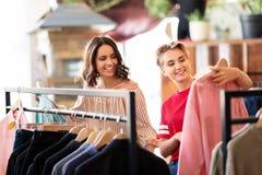 Женщины выбирая одежды на винтажном магазине одежды стоковая фотография