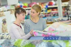 Женщины выбирая ткань в магазине оптовой продажи ткани Стоковая Фотография
