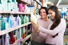 Женщины выбирая уход за волосами в магазине Стоковое Изображение RF