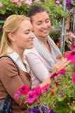 2 женщины выбирая цветки в садовом центре Стоковое Фото