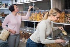 Женщины выбирая чокнутые и высушенные плодоовощи в магазине Стоковая Фотография RF