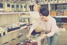 Женщины выбирая чокнутые и высушенные плодоовощи в магазине Стоковое Фото
