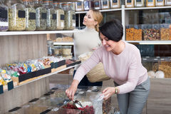 Женщины выбирая чокнутые и высушенные плодоовощи в магазине Стоковое фото RF