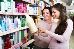 2 женщины выбирая шампунь Стоковые Изображения RF